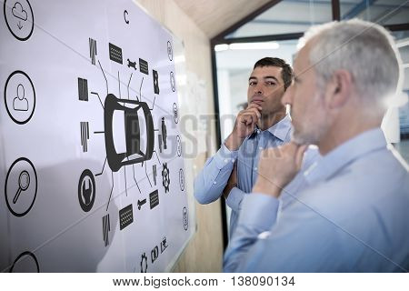 Engineering interface against businessman with hand on chin