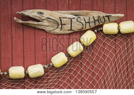 Wooden Carved Sign with Net on House of Fisherman in Icy Strait Alaska