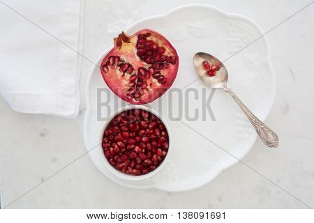 Top-down view of pomegranate seeds in a small bowl set on a dessert plate on white marble with napkin and silver sppon. Three arils (seeds) on spoon and half a pomegranate on plate.