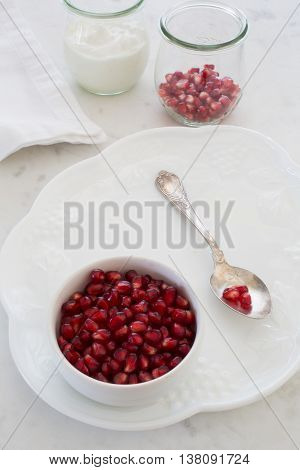 Small bowl of pomegranate arils (pomegranate seeds) set on a dessert plate with an elegant silver spoon. Shot at f/32 with focus throughout. More arils and a container of yogurt sit in the backgroud.