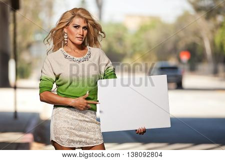 Transgender latina woman pointing to blank sign for advocation messages or hashtags.