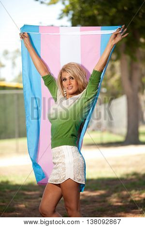 Transgender woman holding pride flag high over head
