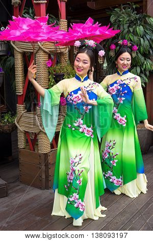 Two Chinese Women In Traditional Oriental Dresses With Parasols In The Form Of Lotus Flowers