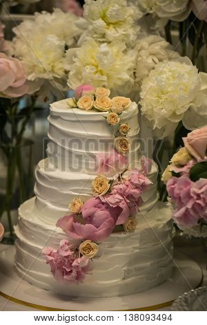 beautiful wedding cake on a background of fresh beautiful flowers