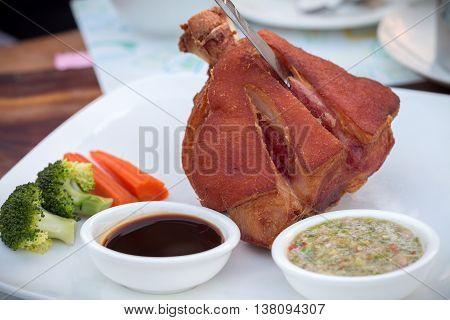 German BBQ pork knuckle served with thai spicy sauce. Pork hock with sauerkraut