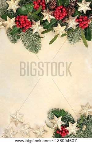 Abstract christmas background border with gold star decorations, holly, ivy, mistletoe and snow covered fir on parchment paper.