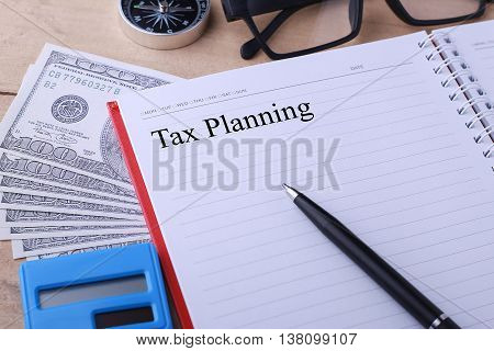Conceptual image. Tax Planning words. Calculator hundred dollar bills pen notebook glasses and compass on wooden table.