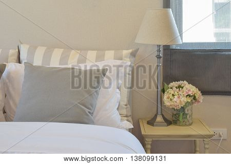 Modern Bedroom Interior With Green Striped Pillow On Bed And Decorative Table Lamp At Home