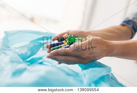 waste recycling, reuse, garbage disposal, environment and ecology concept - close up of hands putting alkaline batteries to rubbish bag