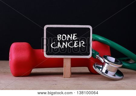 Medical concept - Stethoscope and dumbbell on wood with Bone Cancer word