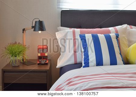 Modern Bedroom Interior With Colorful Striped Pillows And Wooden Reading Lamp On Bedside Table