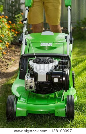 Young man mowing the lawn. Lawn mower