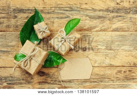 Three gift box with green leaves and blank paper tag on old wooden table