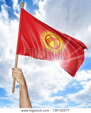 Person's hand holding the Kyrgyzstan national flag and waving it in the sky, 3D rendering