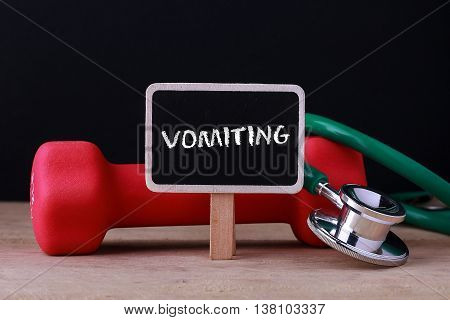 Medical concept - Stethoscope and dumbbell on wood with Vomiting word