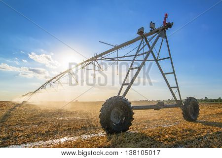 Agricultural irrigation on harvested wheat stubble field in late summer afternoon