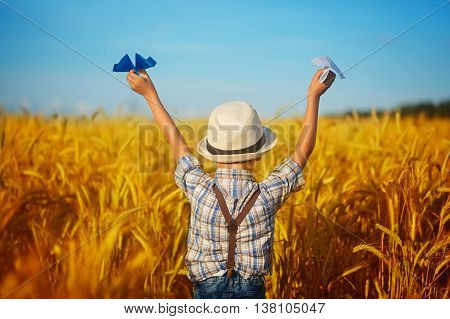 Cute Child Walking In The Wheat Golden Field On A Sunny Summer Day. Boy Starts Paper Plane. Nature I