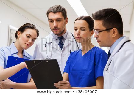 clinic, people, healthcare and medicine concept - group of medics or doctors with clipboards at hospital corridor
