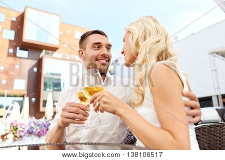 love, dating, people and holidays concept - happy couple drinking wine at open-air restaurant and clinking glasses