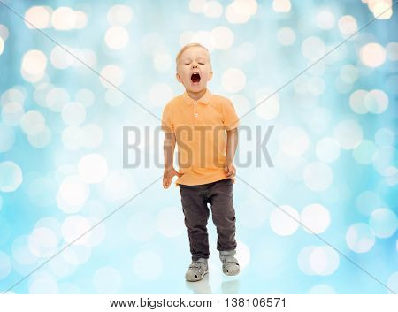 childhood, emotion, expression and people concept - happy little boy in casual clothes shouting, crying or sneezing over blue holidays lights background
