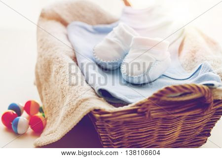 clothing, babyhood, motherhood and object concept - close up of white baby bootees with pile of clothes, towel and rattle for newborn boy in basket