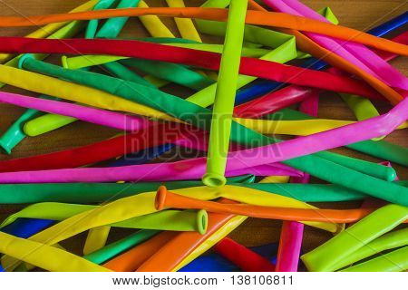 Deflated Color Rubber Air Balloons On Wooden Background