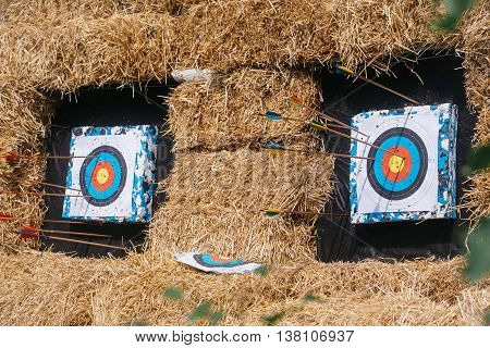 Archery targets with arrows on rural shooting range outdoors on haystack background