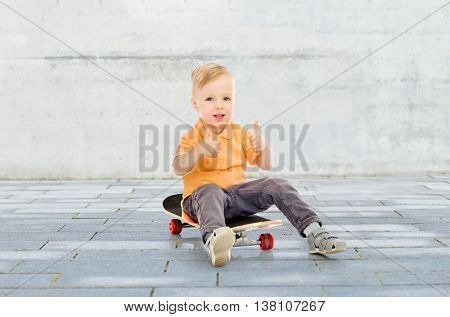 childhood, sport, leisure, gesture and people concept - happy little boy sitting on skateboard and showing thumbs up over city street background