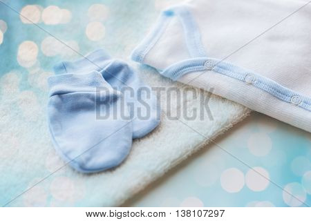 baby clothes, babyhood, motherhood and object concept - close up of white cardigan, mittens and towel for newborn boy