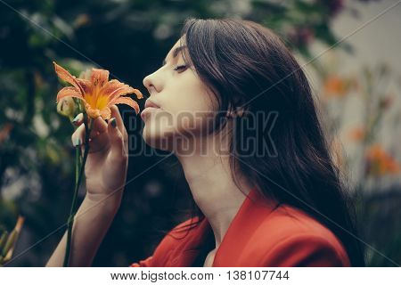 Sensual woman with long brunette hair enjoys fragrance of lily bright orange flower blossoming in summer garden on natural background