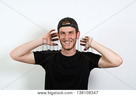Joyful and Smiling Happy Young Adult Male in Dark T-Shirt and Baseball Hat Worn Backwards