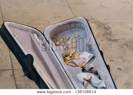 Violin case with paper money and coins on street pavement background