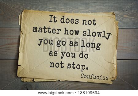 Ancient chinese philosopher Confucius quote on old paper background. It does not matter how slowly you go as long as you do not stop.