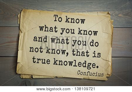 Ancient chinese philosopher Confucius quote on old paper background. To know what you know and what you do not know, that is true knowledge.