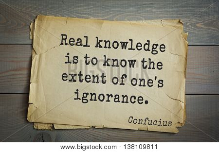 Ancient chinese philosopher Confucius quote on old paper background. Real knowledge is to know the extent of one's ignorance.