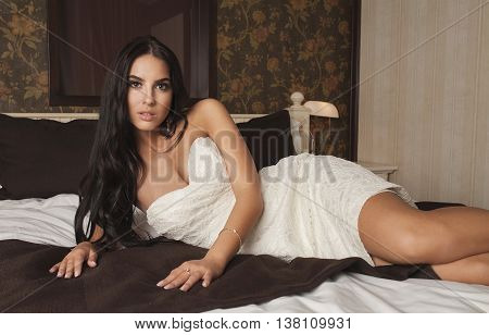 Sexy beautiful brunette woman posing in white dress , looking at camera. Long hair.