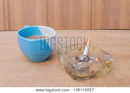 cigarette with ashtray and coffee  on wooden floor background,  Select focus with shallow depth of field
