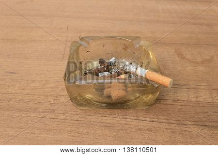cigarette with an ashtray on Wooden background .