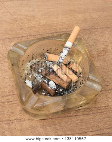 cigarette with an ashtray on Wooden background