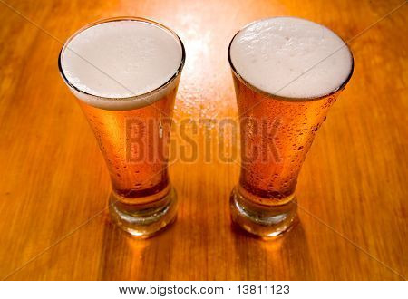 Two Beer Glasses On Wet Wooden Background