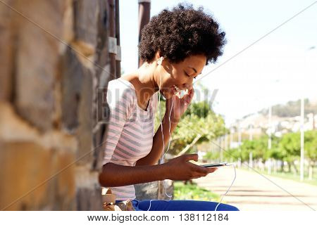 Smiling Woman With Mp3 Player Sitting In Park