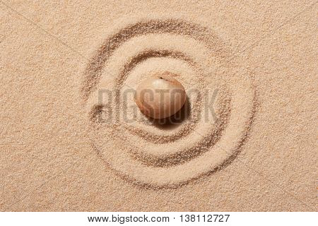 Spiral Drawn On Beach Sand With Pink Round Sea Stone