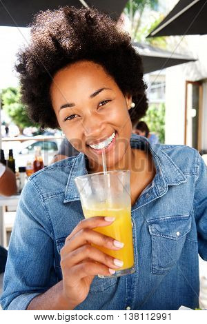 Smiling Woman Drinking Orange Juice At Cafe