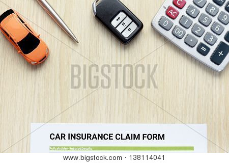 Top view of car insurance claim form with car key car toy and calculator on wooden desk.