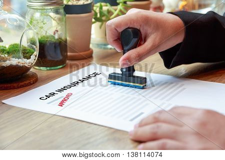 Hands holding rubber stamp with approved car insurance on wooden desk.