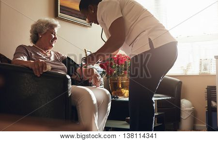 Nurse taking blood pressure of senior patient at home. Female healthcare worker doing routine checkup of a female patient.