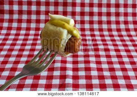 Homemade Mini hot dog (Sausage in the dough) - mini hot dog with mayonnaise and mustard on a fork. Hot dog popular food in America. In Europe, prepare mini hot dogs and fall with various sauces.