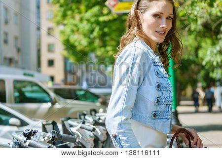 Portrait of beautiful brunette in in denim jacket on street background