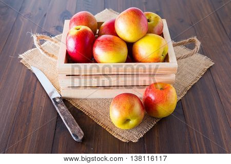Apples in wooden crates placed on the wooden floor.