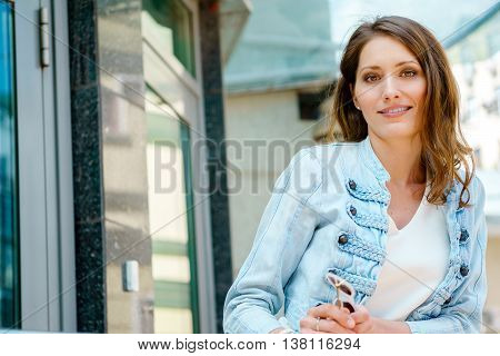 Beautiful brunette woman posing on porch of modern building
